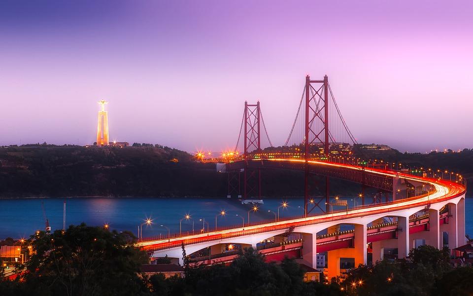 Kilátás az éjszakai Lisszabon egyik látványosságára - az Április 25. Híd és a Krisztus király szobor